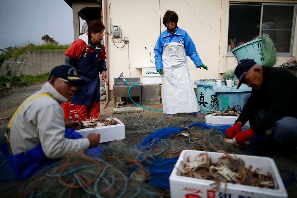 . 80-year-old fisherman Shohei Yaoita (R) removes a crab from a fishing net, after fishing in waters close to the Fukushima Daiichi nuclear power plant, in Iwaki in Fukushima prefecture May 26, 2013. The catch will be used to test for radioactive contamination in the waters near the Fukushima Daiichi nuclear facility. Commercial fishing has been banned near the tsunami-crippled nuclear complex since the March 2011 tsunami and earthquake. The only fishing that still takes place is for contamination research, and is carried out by small-scale fishermen contracted by the government. Picture taken May 26, 2013. REUTERS/Issei Kato