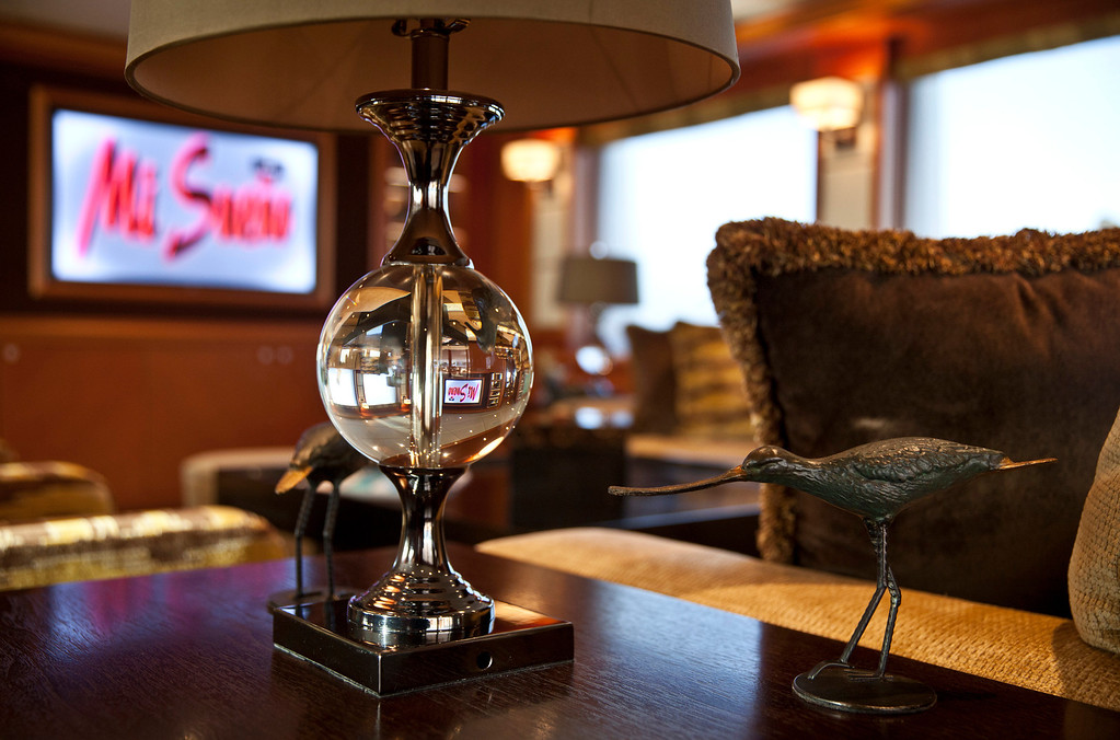 . A lamp stands beside ornaments as a 42 inch flat screen television displays the ship\'s name onboard the 190ft (57.9m) motor yacht Mi Sueno, manufactured by Trinity Yachts LLC, in Nice, France, on Wednesday, Sept. 25, 2013.  Photographer: Balint Porneczi/Bloomberg