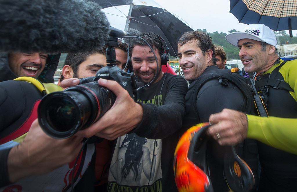 . Brazilian surfer Carlos Burle, second right, and American surfer Garret McNamara, right, watch the video of Burle surfing a big wave at the Praia do Norte, north beach, at the fishing village of Nazare in Portugal\'s Atlantic coast Monday, Oct. 28 2013.  (AP Photo/Miguel Barreira)