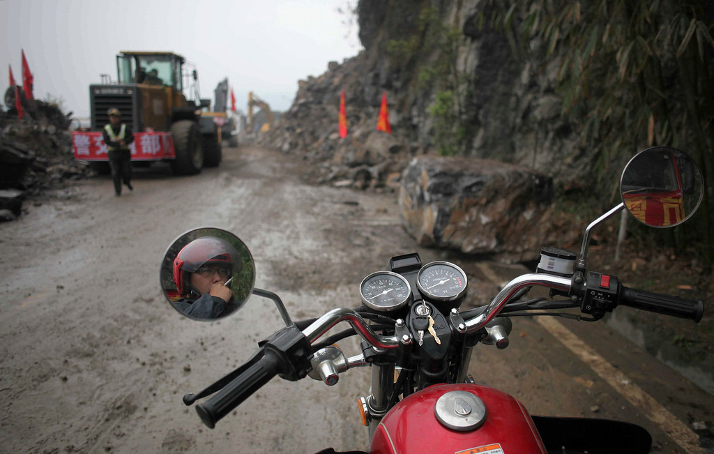 . A man smokes a cigarette on his motorbike as he waits for the rescuers to clean up the road blocked by a landslide after Saturday\'s earthquake, in Baoxing county, Sichuan province April 22, 2013. REUTERS/China Daily