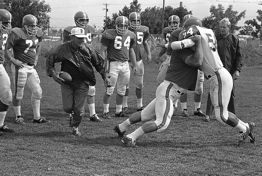 . Coach Lou Saban of the Denver Broncos (with ball) runs his young charges through a practice session in Denver, Colorado on August 25, 1967. Average age of the Broncos is 23. Saban has a 10-year contract with the Broncos for a reported $500,000. In the youth movement on the Broncos 11 rookies are being counted on as linebackers on defense. (AP Photo/Robert D. Scott)