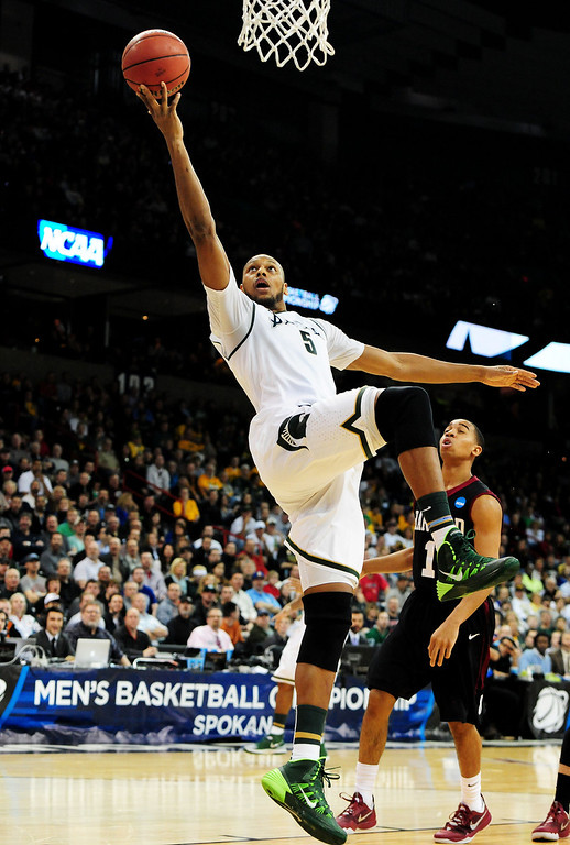 . SPOKANE, WA - MARCH 22:  Adreian Payne #5 of the Michigan State Spartans shoots over Siyani Chambers #1 of the Harvard Crimson in the first half during the Third Round of the 2014 NCAA Basketball Tournament at Spokane Veterans Memorial Arena on March 22, 2014 in Spokane, Washington.  (Photo by Steve Dykes/Getty Images)