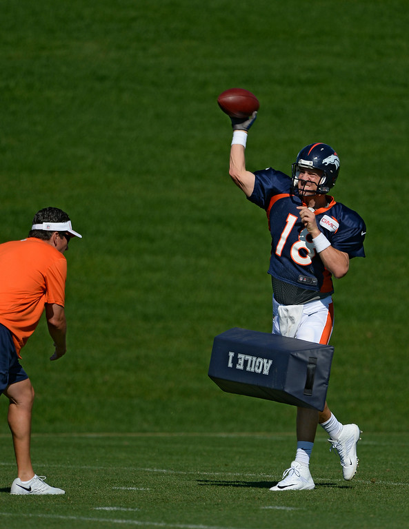 . Denver Broncos quarterback Peyton Manning (18) runs through drills as he gets hit by a pad thrown by quarterbacks coach Greg Knapp during practice at the Denver Broncos 2014 training camp August 12, 2014 at Dove Valley. (Photo by John Leyba/The Denver Post)