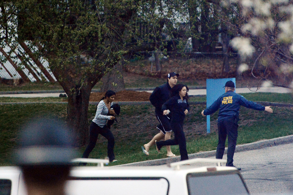 . WATERTOWN, MA - APRIL 19: Law enforcement evacuate people away from an area reportedly where a suspect is hiding on April 19, 2013 in Watertown, Massachusetts. After a car chase and shoot out with police, one suspect in the Boston Marathon bombing, Tamerlan Tsarnaev, 26, was shot and killed by police early morning April 19, and a manhunt is underway for his brother and second suspect, 19-year-old Dzhokhar A. Tsarnaev. The two men are suspects in the bombings at the Boston Marathon on April 15, that killed three people and wounded at least 170.  (Photo by Darren McCollester/Getty Images)