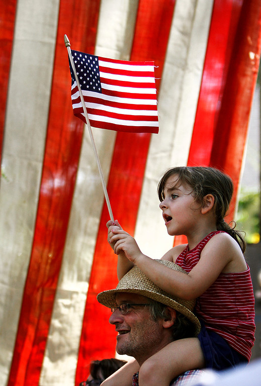 . Ila Gocke, 5, sings patriotic songs on Thursday, July 4, 2013, while attending the annual Watts Hospital-Hillandale Fourth of July celebration with her father, Matt Gocke, and mother, Dara Shain, in Durham, N.C.  The annual parade was started by Alice Walker in 1950.  (AP Photo/The Herald-Sun, Christine T. Nguyen)
