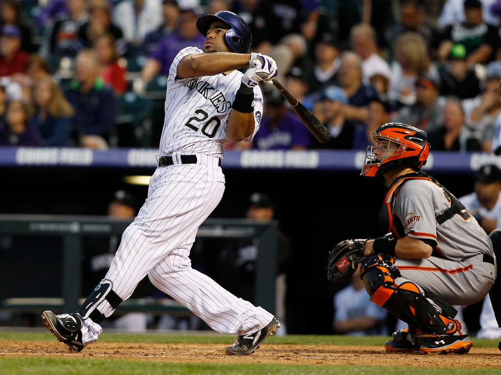 . Colorado Rockies\' Wilin Rosario, left, follows the flight of his two-run home run with San Francisco Giants catcher Buster Posey in the fifth inning of a baseball game in Denver, Saturday, May 18, 2013. (AP Photo/David Zalubowski)