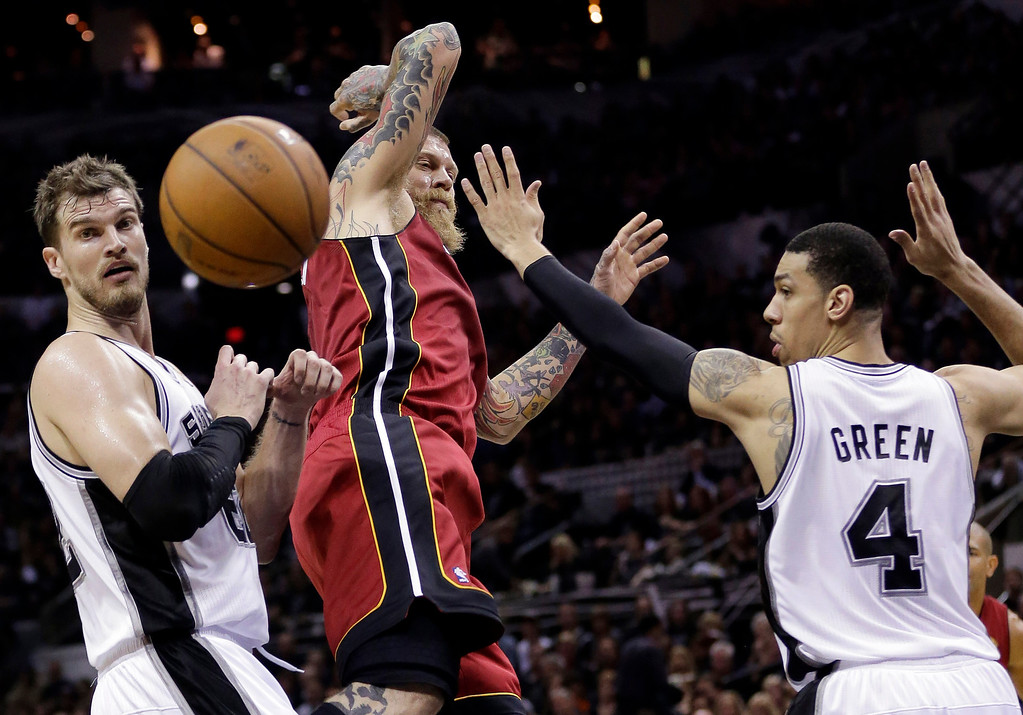 . From left, San Antonio Spurs center Tiago Splitter, Miami Heat forward Chris Andersen and guard Danny Green lose the ball during the first half in Game 1 of the NBA basketball finals on Thursday, June 5, 2014, in San Antonio. (AP Photo/Eric Gay)