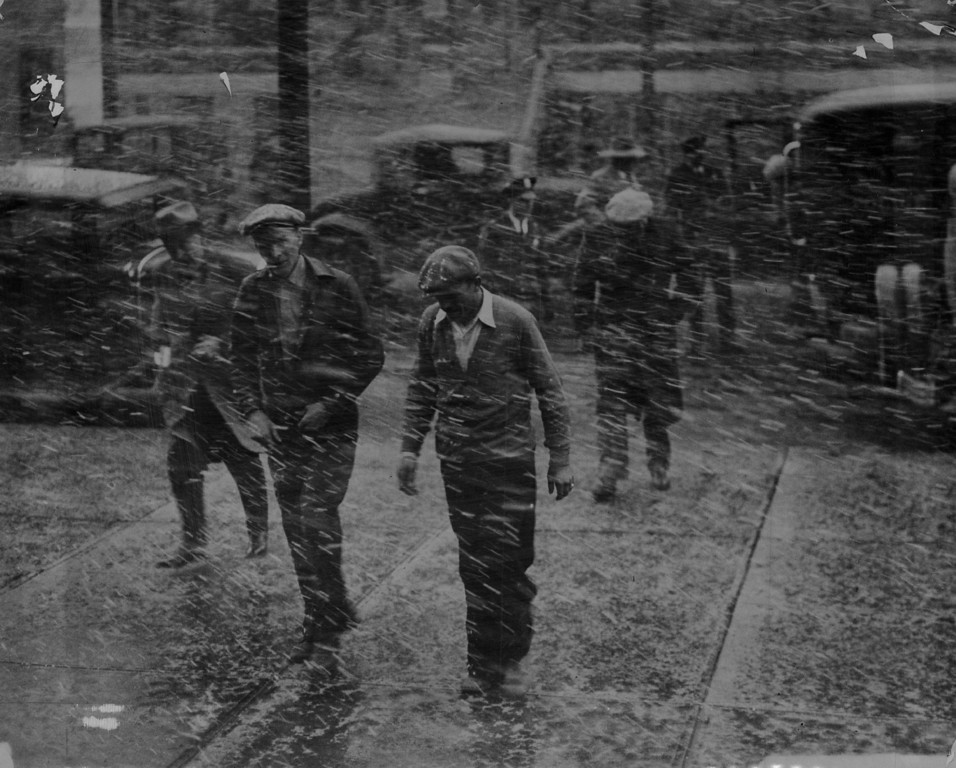 . MAR 27 1932 - Gangsters (Denver) - It\'s Not Always Fair Weather when gangsters get together. This picture was snapped by a Denver Post photographer, Saturday afternoon, when a coterie of alleged liquor law violators rounded up by police and federal agents early Saturday arrived at the federal building simultaneously with a driving snowstorm. The alleged gangsters were being taken to the office of the United Stated commissioner for arraignment. A few of them may be seen in the foreground, with uniformed guardians of the law in the dim background. (Denver Post digital archive photo)