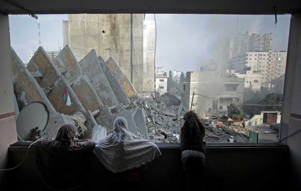. A Palestinian family looks from a window to the rubble of the collapsed 15-story Basha Tower following early morning Israeli airstrikes in Gaza City, Tuesday, Aug. 26, 2014. Israel bombed two Gaza City high-rises with dozens of homes and shops Tuesday, collapsing the 15-story Basha Tower and severely damaging the Italian Complex in a further escalation in seven weeks of cross-border fighting with Hamas. (AP Photo/Khalil Hamra)