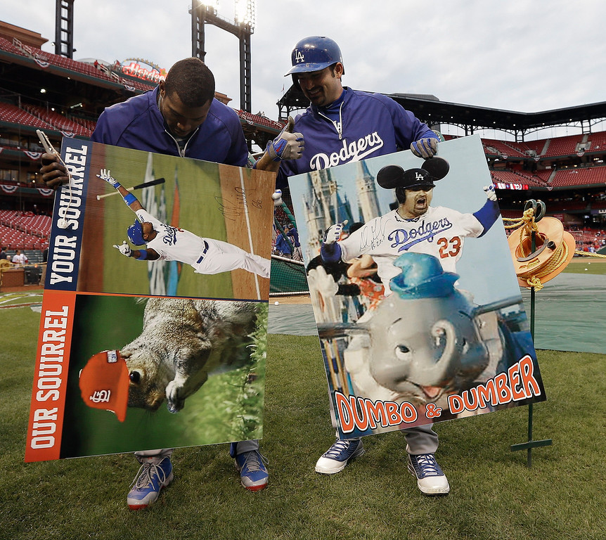 . Los Angeles Dodgers\' Yasiel Puig and Adrian Gonzalez hold up signs they autographed before  Game 6 of the National League baseball championship series against the St. Louis Cardinals, Friday, Oct. 18, 2013, in St. Louis. (AP Photo/Charlie Neibergall)