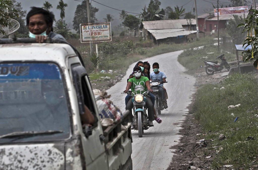 . Motorists wear masks while passing through an area covered by ash after Mount Sinabung erupted spewing volcanic materials in Karo district on November 14, 2013 in Medan, Sumatra, Indonesia. Up to 4,300 residents have been evacuated from five villages in North Sumatra due to the volcanic eruptions of Mount Sinabung. The volcano has been erupting for several days, spewing ash and lava 2.5 miles into the sky.  (Photo by Ulet Ifansasti/Getty Images)