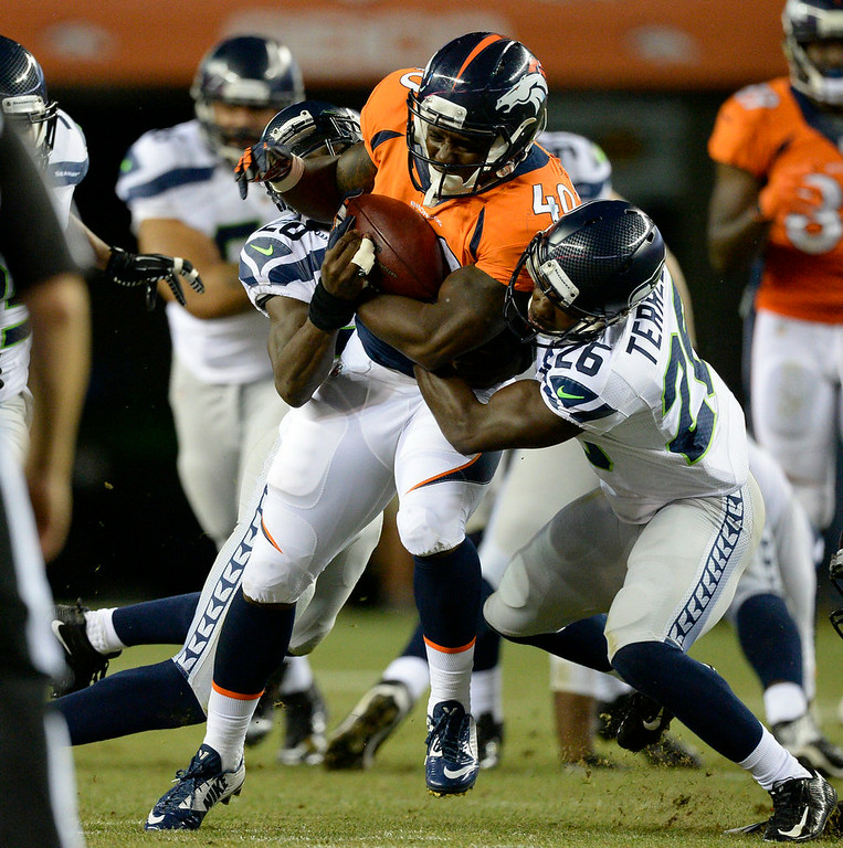 . Denver Broncos running back Juwan Thompson (40) picks up a big gain before he is brought down by Seattle Seahawks cornerback Jeremy Lane (20) and Seattle Seahawks fullback Michael Robinson (26) during the third quarter August 7, 2014 at Sports Authority Field at Mile High Stadium.  (Photo by John Leyba/The Denver Post)