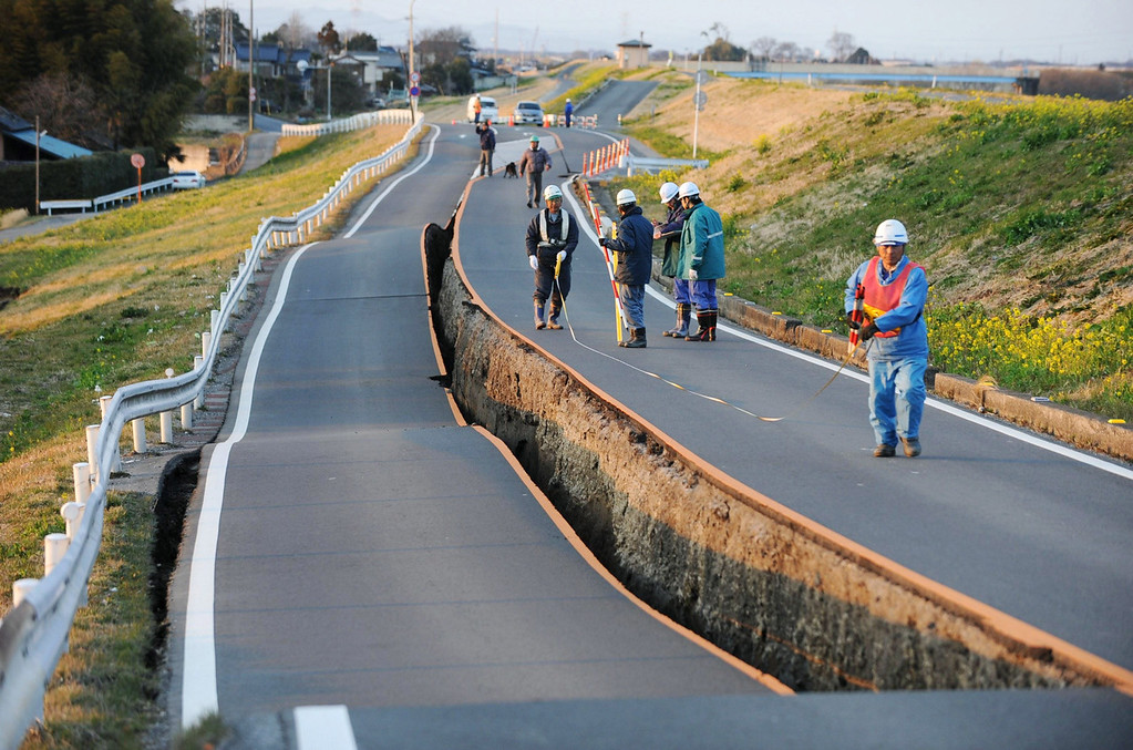 . Workers inspect a caved-in section of a prefectural road in Satte, Saitama Prefecture, after one of the largest earthquakes ever recorded in Japan slammed its eastern coast Friday, March 11, 2011. (AP Photo/Saitama Shimbun via kyodo News)