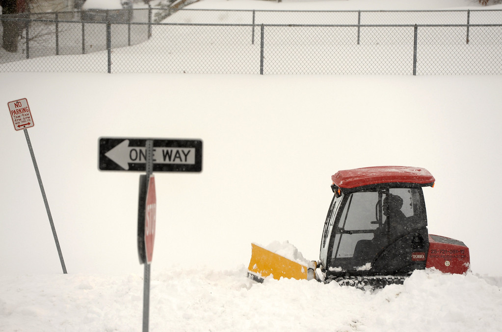 . A Baltimore County worker clears snow from a walkway in Towson, Md. Thursday, Feb. 13, 2014. The storm was the biggest in Maryland in four years, prompting a state of emergency declaration by the governor. (AP Photo/Steve Ruark)