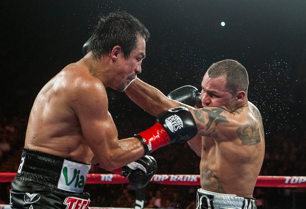 . Mike Alvarado, right, and Juan Manuel Márquez, of Mexico, exchange punches in the seventh round of a WBO welterweight title boxing match at the Forum in Inglewood, Calif., Saturday, May 17, 2014. Márquez won the title.  (AP Photo/Ringo H.W. Chiu)