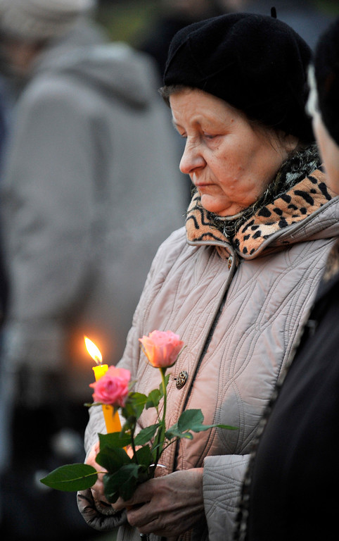 . A woman holds a candles and flowers outside the collapsed Maxima supermarket in Riga, Latvia, Friday, Nov. 22, 2013. The reason for the collapse during shopping rush-hour Thursday was still not known but rescue and police officials said that possible theories include building\'s design flaws and poor construction work. (AP Photo/ Roman Koksarov)