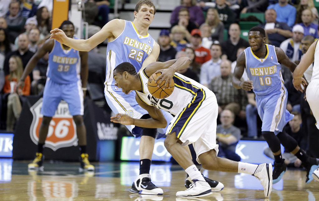 . Utah Jazz\'s Alec Burks (10) drives against Denver Nuggets\' Timofey Mozgov, of Russia, (25) while teammates Kenneth Faried (35) and Nate Robinson (10) look on in the second half during an NBA basketball game Monday, Jan. 13, 2014, in Salt Lake City. The Jazz won 118-103. (AP Photo/Rick Bowmer)