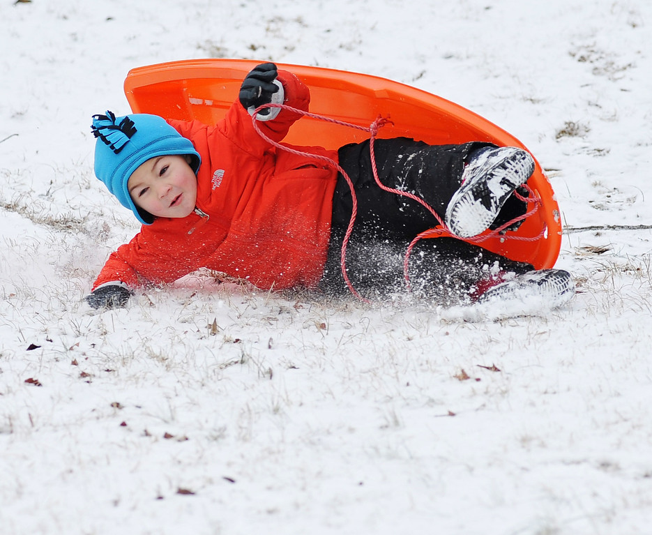 . Guy Fruge falls off his sled at Avent Park in Oxford, Miss. on Tuesday, Feb. 11, 2014. Weather that left a thin layer of ice covered by snow has closed area schools. (AP Photo/Oxford Eagle, Bruce Newman)