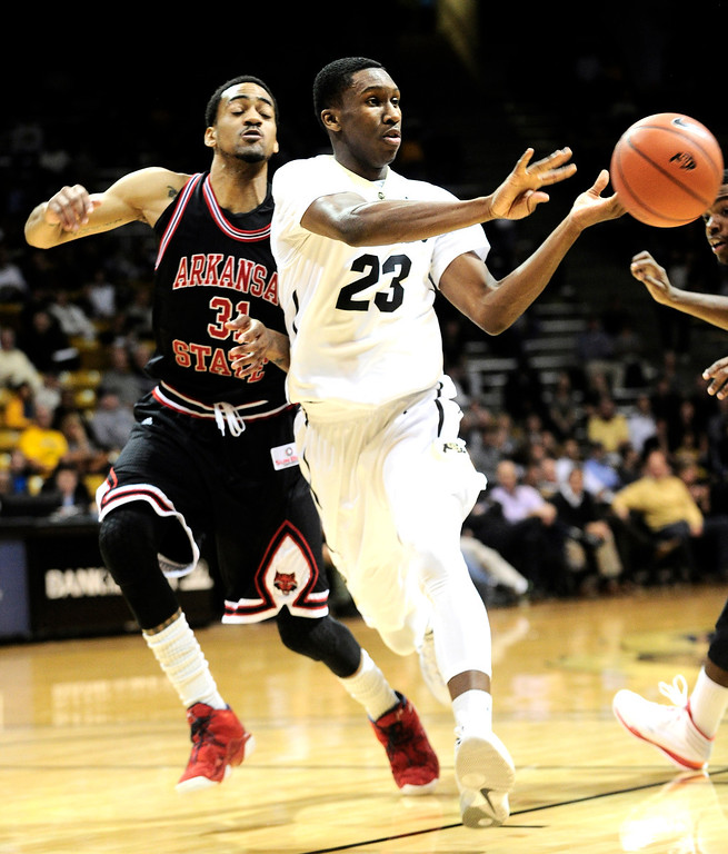. University of Colorado\'s Jaron Hopkins (23) passes the ball against Arkansas State\'s Melvin Johnson (31) during their game at the Coors Events Center on the CU Boulder Campus in Boulder, Colorado on November 18, 2013.  Photo by Paul Aiken / The Boulder Daily Camera.