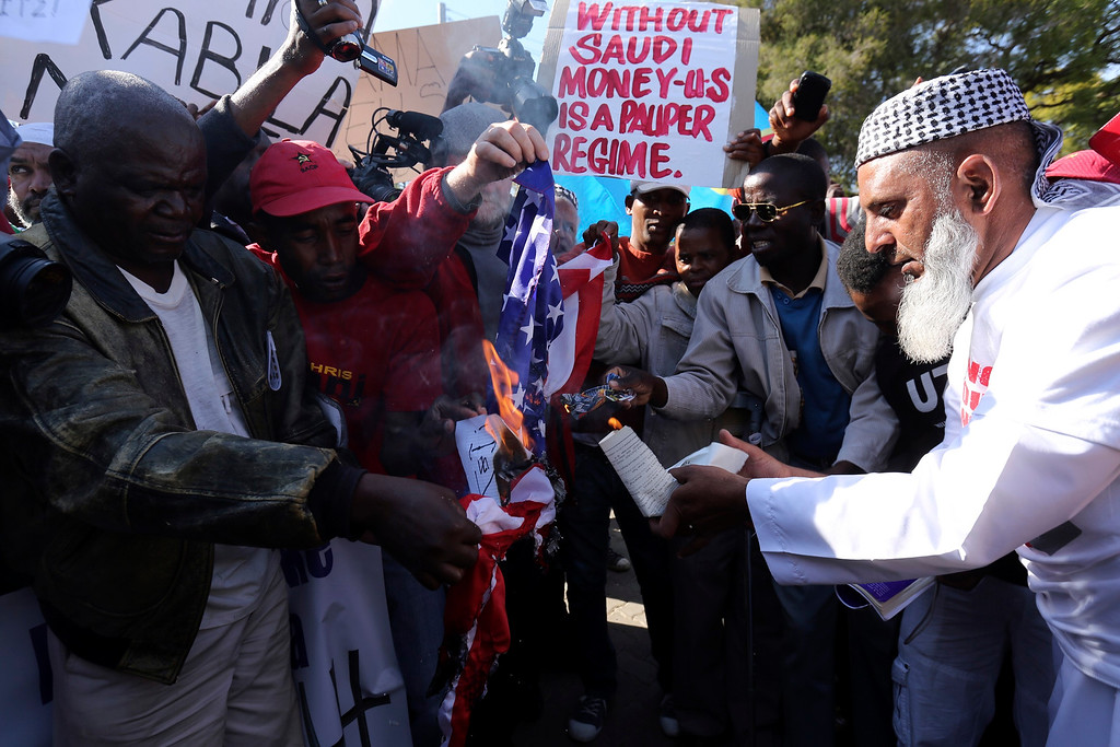 . Protesters burn a U.S. flag as they protest against the visit of U.S. President Barack Obama, in Pretoria, June 28, 2013. Obama heads to South Africa on Friday hoping to see ailing icon Nelson Mandela, after wrapping up a visit to Senegal that focused on improving food security and promoting democratic institutions. Obama is in the middle of a three-country tour of Africa that the White House hopes will compensate for what some view as years of neglect by the administration of America\'s first black president. REUTERS/Siphiwe Sibeko