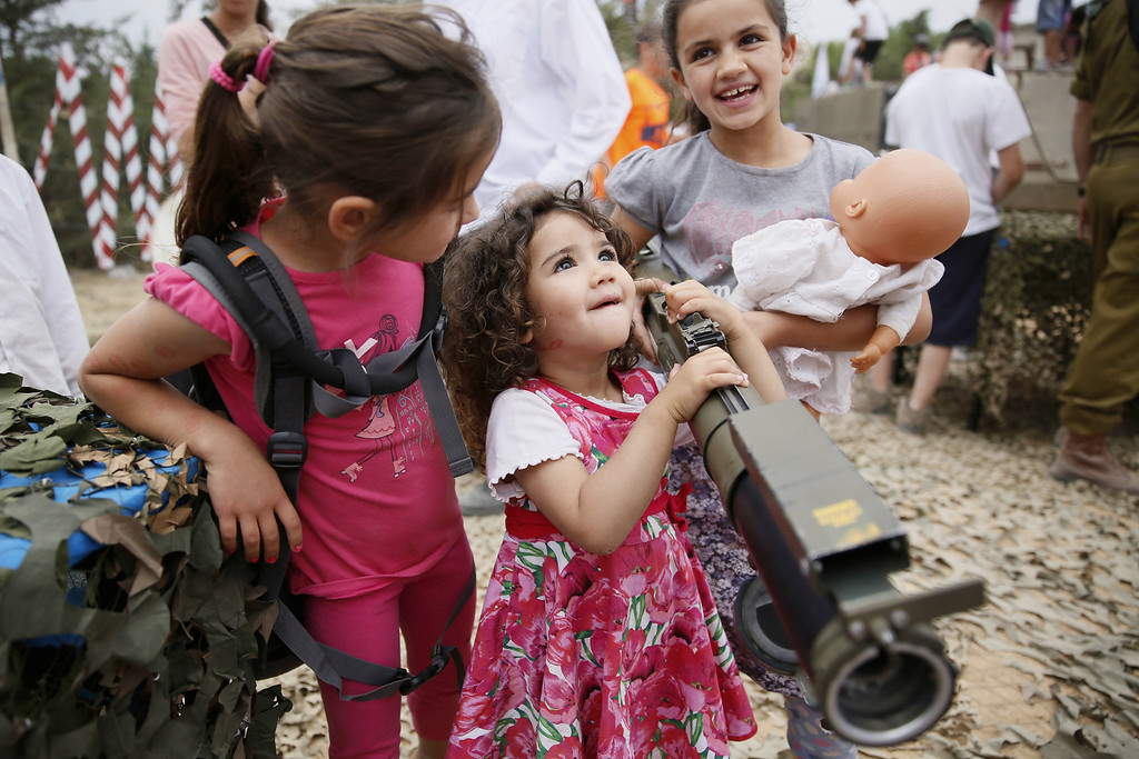 . An Israeli child holds a rocket launcher as another holds her doll during a traditional military weapon display to mark the 66th anniversary of Israel\'s Independence at the West Bank settlement of Efrat on May 6, 2014 near the biblical city of Bethlehem. Israelis are marking Independence Day, celebrating the 66th year since the founding of the Jewish State in 1948 according to the Jewish calendar. AFP PHOTO/GALI TIBBON