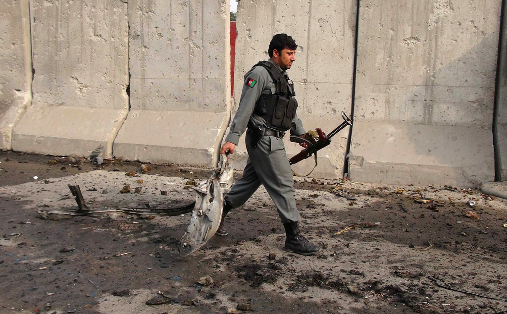 . A member of the Afghan security forces carries a piece of mangled wreckage at the site of a suicide attack in Jalalabad on October 12, 2013.  A suicide bomber killed two policemen when he slammed an explosives-laden car into a police headquarters in east Afghanistan, underlining the country\'s instability as US Secretary of State John Kerry visited Kabul. OMAR GUL/AFP/Getty Images