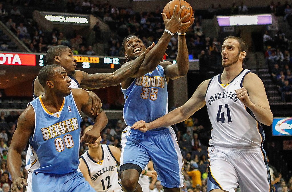 . Denver Nuggets forward Kenneth Faried (35) with teammate Darrell Arthur (00) gets fouled on the way to the basket by Memphis Grizzlies forward Ed Davis, left, with help by Kosta Koufos (41) in the first half of an NBA basketball game Friday, April 4, 2014, in Memphis, Tenn. (AP Photo/Lance Murphey)