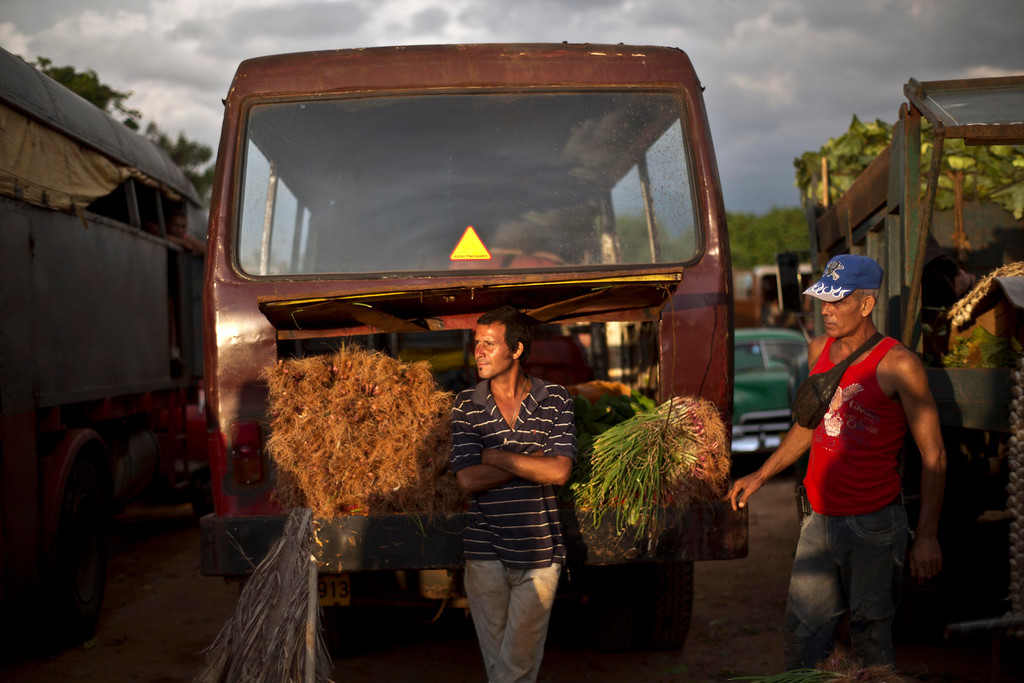 . In this Sept. 30, 2013 photo, onion vendors wait for customers at the 114th Street Market on the outskirts of Havana, Cuba. Produce is brought in by growers themselves and by transportation specialists who make a living by buying crops far away and hauling them to Havana, the island\'s biggest and most important market. (AP Photo/Ramon Espinosa)