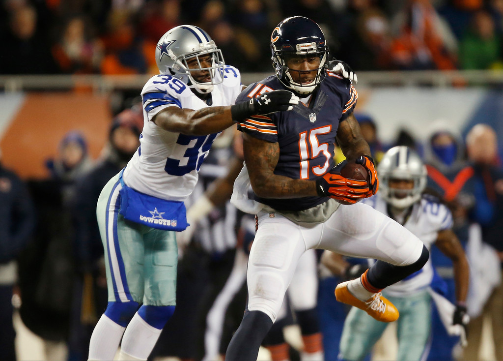 . Chicago Bears wide receiver Brandon Marshall (15) makes a catch under pressure from Dallas Cowboys cornerback Brandon Carr (39) during the first half of an NFL football game, Monday, Dec. 9, 2013, in Chicago. (AP Photo/Charles Rex Arbogast)