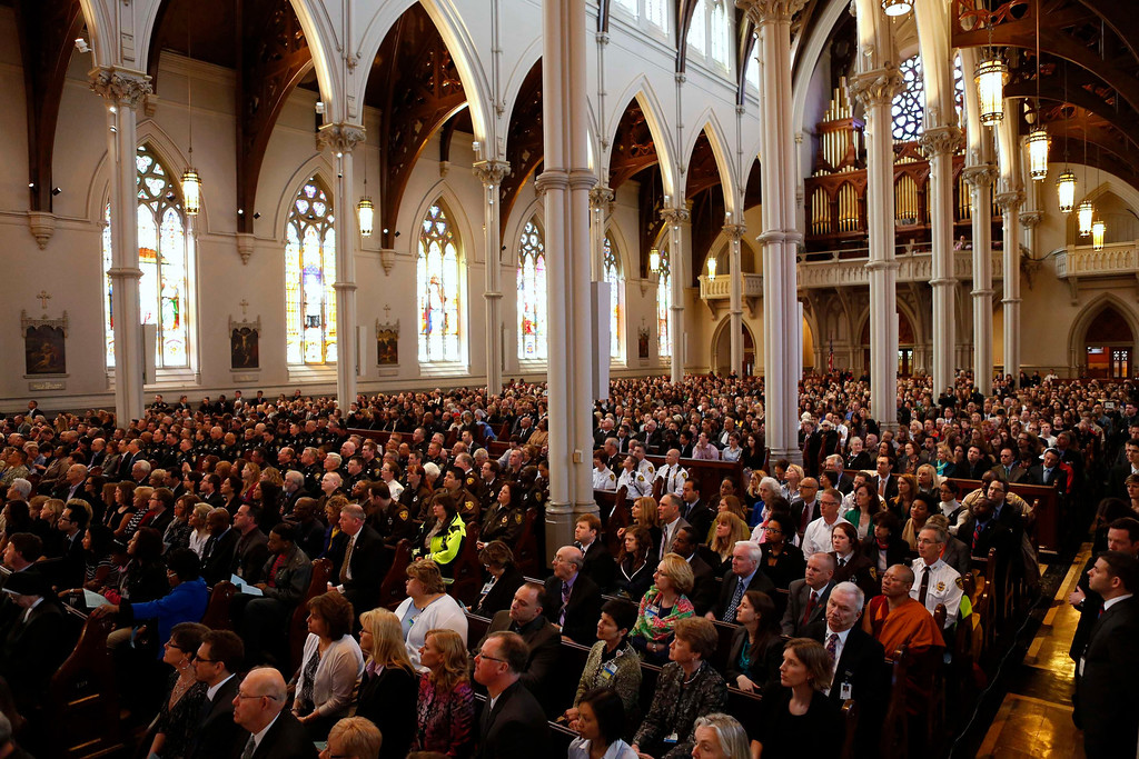 ". People attend the interfaith memorial service at the Cathedral of the Holy Cross for the victims of the Boston Marathon bombing in Boston, Massachusetts April 18, 2013.  Obama told a memorial service for the Boston bombing victims that ""we will find\"" whoever carried out the attack that killed three people as investigators search for two men seen on a video of the scene shortly before the blasts. REUTERS/Kevin Lamarque"