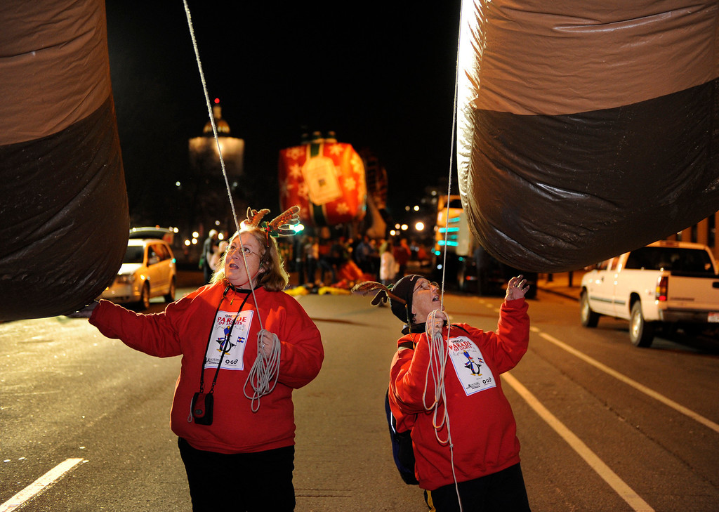 . Volunteers Lane Brown, left, and Kathleen McGovern, right, helped tether the Rudolph balloon the ground Friday night before the parade. The annual Parade of Lights filed past the illuminated City and County building in downtown Denver Friday night, November 30. 2012. The parade with 11 floats, 7 bands, 5 giant balloons and more lights than anyone could count, had enough holiday spirit for everyone. Karl Gehring/ The Denver Post