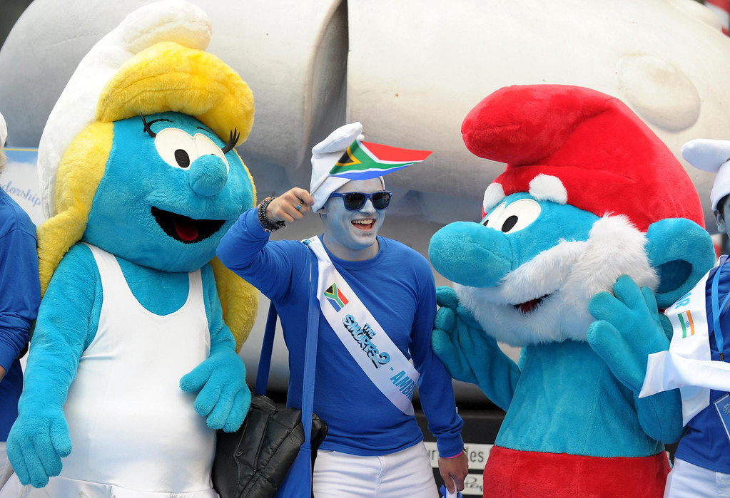 """. A Smurf Ambassador poses with life-size characters of Smurfette (L) and Papa Smurf (R) during a celebration for the birthday of Peyo, the creator of the Smurfs, on \""""Global Smurfs Day\"""" in Brussels June 22, 2013. The event was held ahead of the release of the film \""""The Smurfs 2\"""", according to organisers. REUTERS/Laurent Dubrule"""