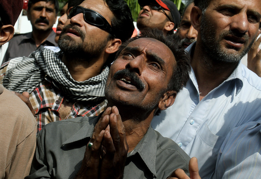 . Pakistanis pray for people stranded in a building that caught on fire, in Lahore, Pakistan, Thursday, May 9, 2013. (AP Photo/K.M. Chaudary)