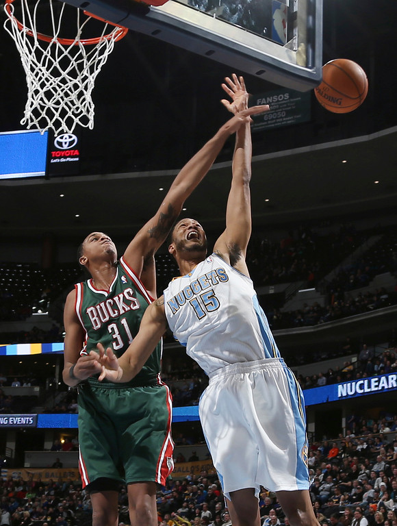 . Milwaukee Bucks forward John Henson, left, stops shot by Denver Nuggets forward Anthony Randolph during the third quarter of the Nuggets\' 110-100 victory in an NBA basketball game in Denver on Wednesday, Feb. 5, 2014. (AP Photo/David Zalubowski)
