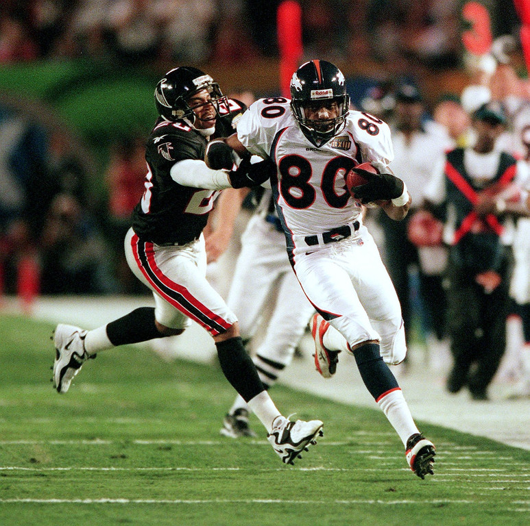 . Denver Broncos Rod Smith makes a 41 yard pass  reception and run as Atlanta Falcons Michael Booker gives a push  during the a first quarter drive that setup the Broncos first  touchdown of Super Bowl XXXIII at Pro Player Stadium.  (Karl Gehring/The Denver Post)