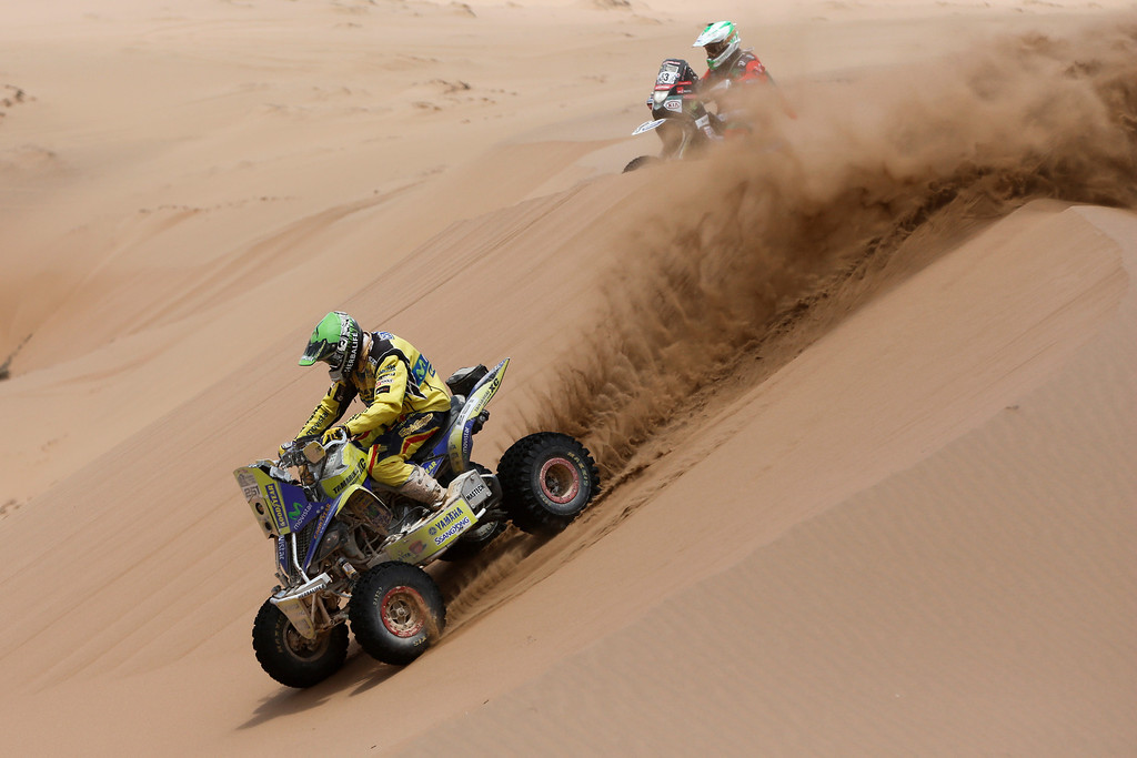 . Yamaha rider Ignacio Casale of Chile, left, rides ahead of Honda rider Lucas Bonetto of Argentina, top, through the dunes during the twelfth stage of the Dakar Rally between the cities of El Salvador and La Serena, Chile, Friday, Jan. 17, 2014. (AP Photo/Victor R. Caivano)
