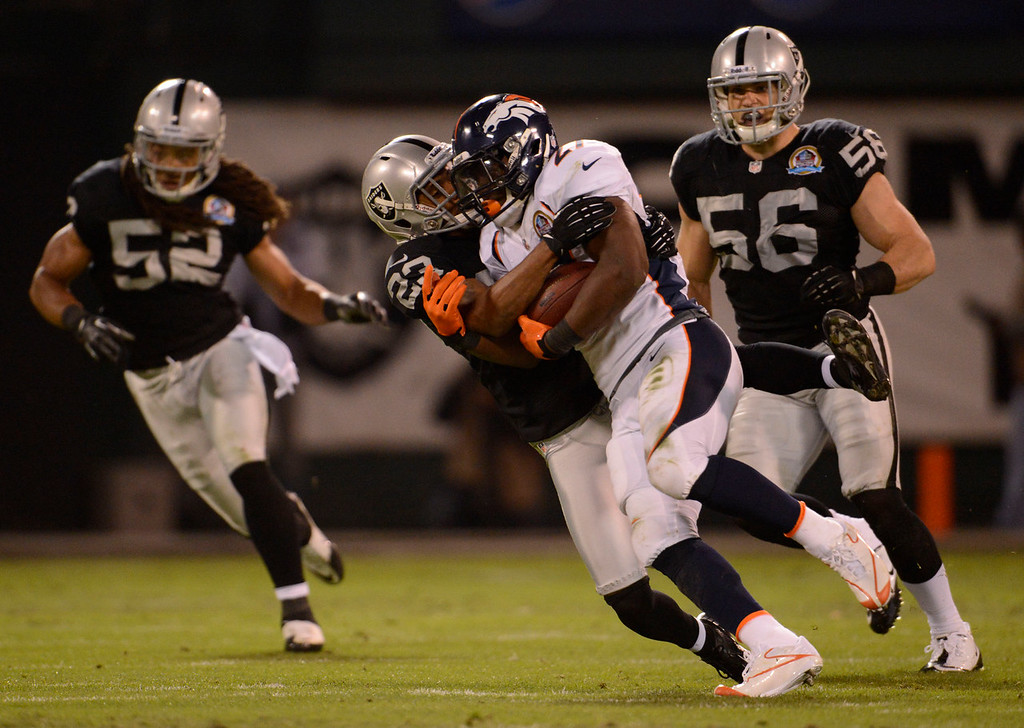 . Oakland Raiders defensive back Joselio Hanson (23) tackles Denver Broncos running back Knowshon Moreno (27) after a short gain in the first quarter Thursday, December 6, 2012 during Thursday Night Football at O.c Coliseum in Oakland  John Leyba, The Denver Post