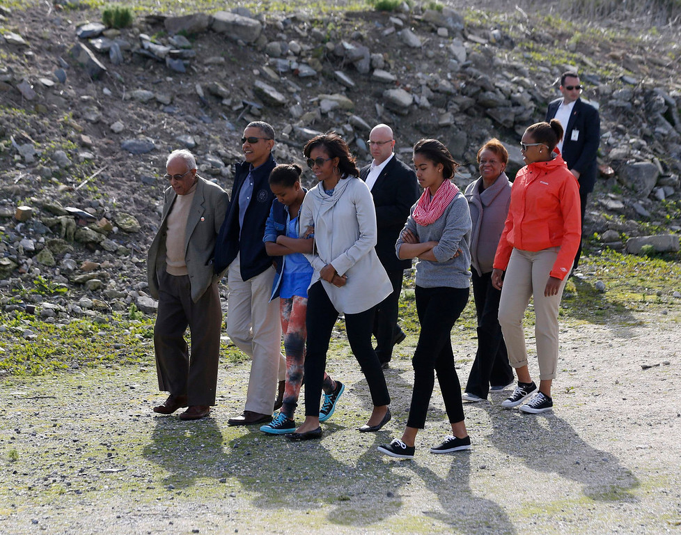 . U.S. President Barack Obama walks with his family as they visit the rock quarry labor camp where Nelson Mandela was forced to work as a prisoner on Robben Island near Cape Town, South Africa on June 30, 2013. The Obamas visited the bleak former prison island off the coast of South Africa on Sunday to pay tribute to ailing anti-apartheid hero Mandela and set the stage for a speech urging Africans to strive for prosperity and democracy. Pictured with the first family is their guide Ahmed Kathrada (L).    REUTERS/Jason Reed