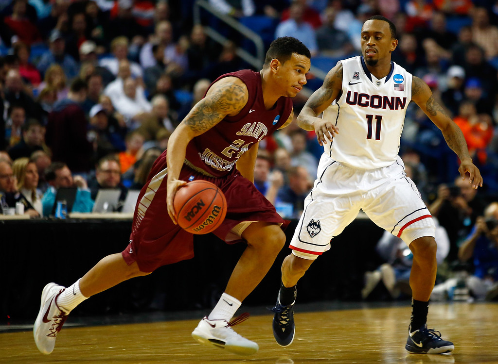 . BUFFALO, NY - MARCH 20: Chris Wilson #24 of the Saint Joseph\'s Hawks carries the ball as Ryan Boatright #11 of the Connecticut Huskies defends during the second round of the 2014 NCAA Men\'s Basketball Tournament at the First Niagara Center on March 20, 2014 in Buffalo, New York.  (Photo by Jared Wickerham/Getty Images)