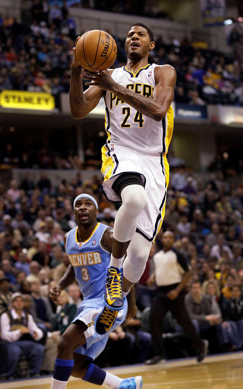. Indiana Pacers forward Paul George, right, goes to the basket in front of Denver Nuggets guard Ty Lawson during the second half of an NBA basketball game in Indianapolis, Friday, Dec. 7, 2012. The Nuggets won 92-89. (AP Photo/AJ Mast)