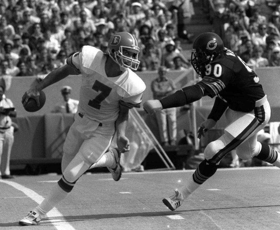 . Denver Broncos\' John Elway looks back as Chicago Bears\' Al Harris Closes in on him during the second quarter in Chicago, Oct. 2, 1983.  (AP Photo/Fred Jewell)