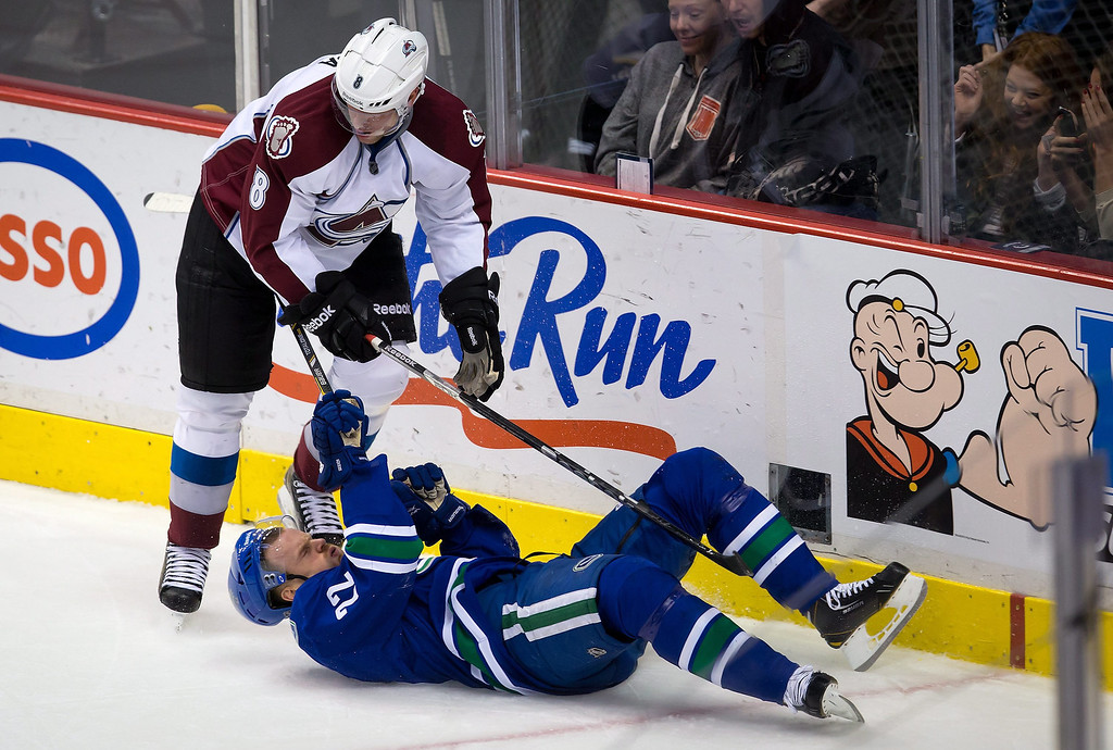 . Colorado Avalanche\'s Jan Hejda, left, of the Czech Republic, checks Vancouver Canucks\' Daniel Sedin, of Sweden, to the ice during the second period  of an NHL hockey game in Vancouver, British Columbia, Thursday, March 28, 2013. (AP Photo/The Canadian Press, Darryl Dyck)