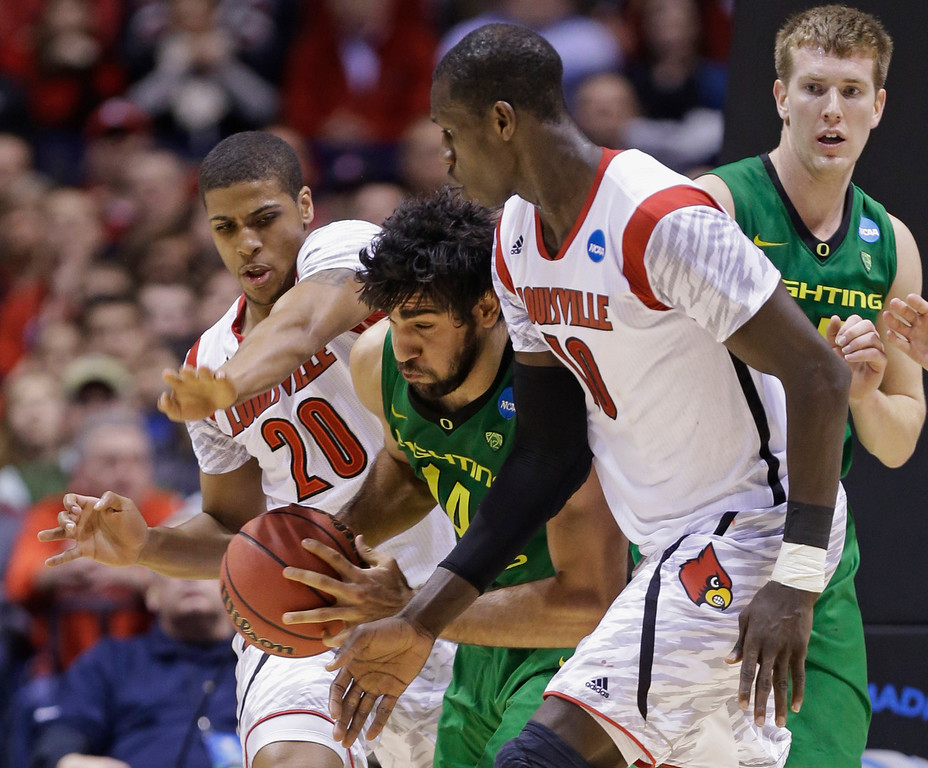 . Oregon forward Arsalan Kazemi battles to drive through Louisville guard Wayne Blackshear (20) and center Gorgui Dieng (10) during the second half of a regional semifinal in the NCAA college basketball tournament, Friday, March 29, 2013, in Indianapolis. Louisville won 77-69. (AP Photo/Michael Conroy)