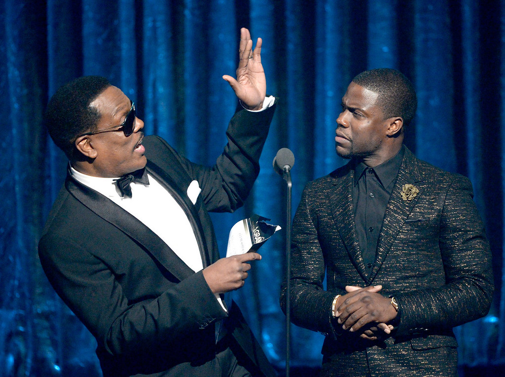 . Singer Charlie Wilson (L) and comedian Kevin Hart speak onstage during the 56th GRAMMY Awards at Staples Center on January 26, 2014 in Los Angeles, California.  (Photo by Kevork Djansezian/Getty Images)