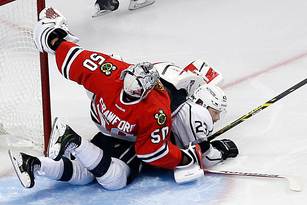 . Chicago Blackhawks goalie Corey Crawford (50) collides with Los Angeles Kings right wing Dustin Brown (23) during the second period in Game 7 of the Western Conference finals in the NHL hockey Stanley Cup playoffs Sunday, June 1, 2014, in Chicago. (AP Photo/Charles Rex Arbogast)