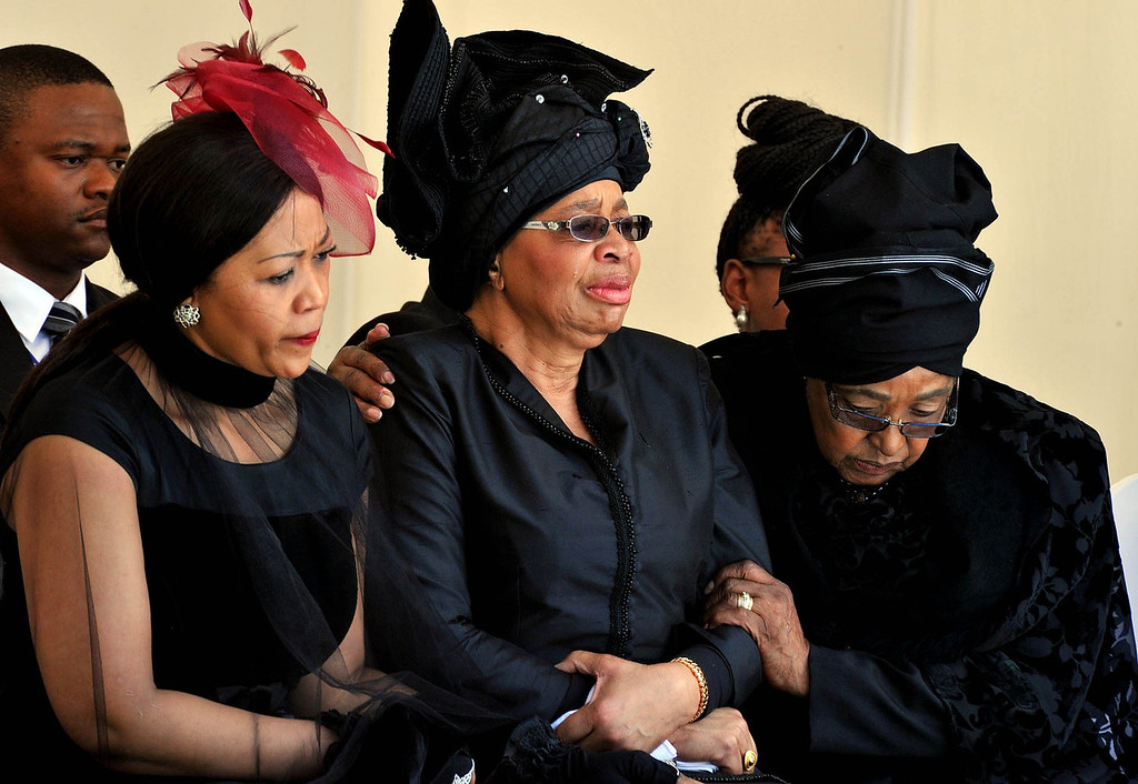 . From left: Tobeka Zuma, Nelson Mandelaís widow Graca Machel, and Winnie Madikizela-Mandela, Nelson Mandela\'s former wife, watch as former South African President Nelson Mandela\'s casket arrives at his burial site following his funeral service in Qunu, South Africa, Sunday, Dec. 15, 2013. (AP Photo/Elmond Jiyane, GCIS)