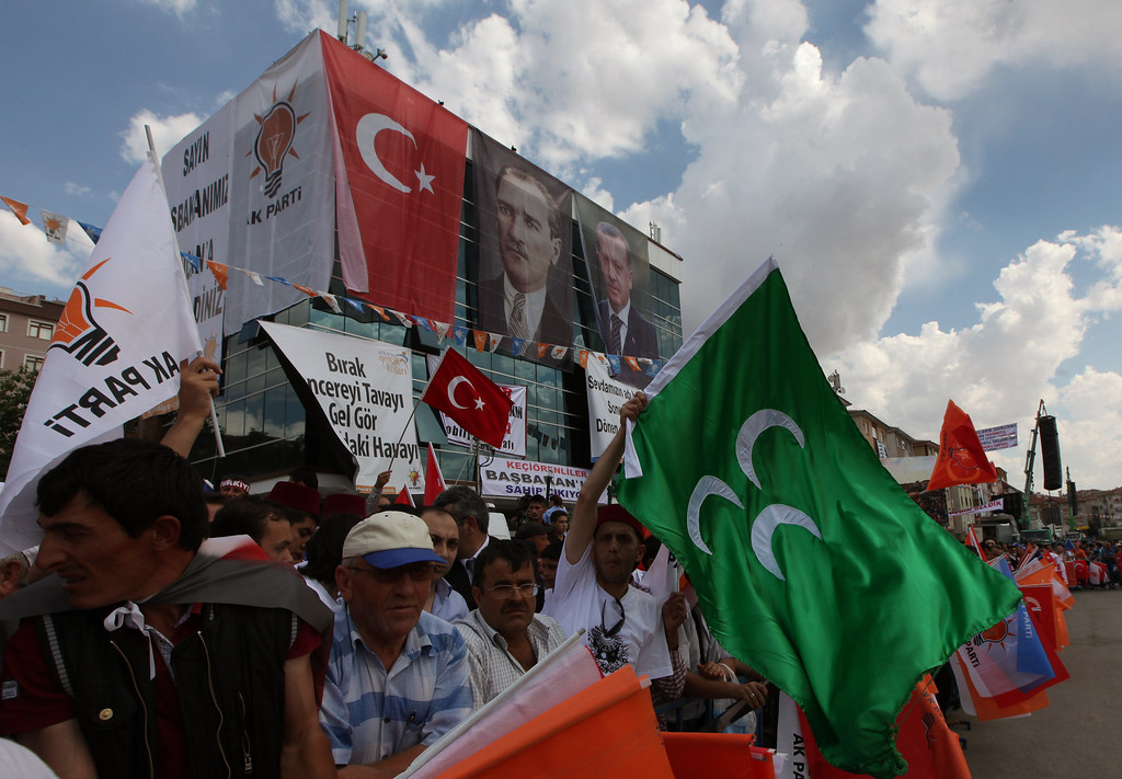 . Supporters of Turkish Prime Minister Recep Tayyip Erdogan wave flags before he arrives to address a party rally outside Ankara, Turkey, Saturday, June 15, 2013. Erdogan said Friday he has asked a small delegation of protesters to convince those occupying a park to withdraw, adding that he is hopeful their protest action would end soon. The green flag is the flag of Ottoman Empire.(AP Photo/Burhan Ozbilici)
