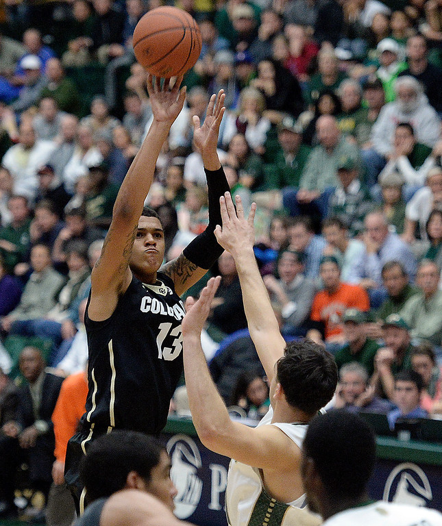 . CU\'s Dustin Thomas takes a shot over J.J. Avila during an NCAA game against CSU on Tuesday, Dec. 3, 2013, at the Moby Arena in Fort Collins.
