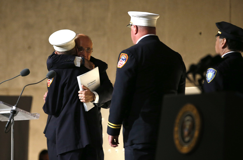 ". Former New York City Mayor Rudy Giuliani (back L) hugs retired New York City Fire fighter Mickey Kross as he greeted first responders to the scene of the World Trade Center attacks on September 11, 2001, during the opening ceremony for the National September 11 Memorial Museum at ground zero May 15, 2014 in New York City. The museum spans seven stories, mostly underground, and contains artifacts from the attack on the World Trade Center Towers on September 11, 2001 that include the 80 ft high tridents, the so-called ""Ground Zero Cross,\"" the destroyed remains of Company 21\'s New York Fire Department Engine as well as smaller items such as letter that fell from a hijacked plane and posters of missing  loved ones projected onto the wall of the museum. The museum will open to the public on May 21.  (Photo by Mike Segar-Pool/Getty Images)"