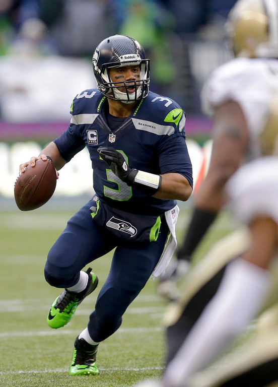 . Seattle Seahawks quarterback Russell Wilson rolls out against the New Orleans Saints during the first half of an NFC divisional playoff NFL football game in Seattle, Saturday, Jan. 11, 2014. (AP Photo/Ted S. Warren)
